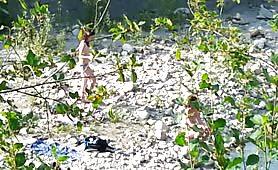 Guardone riprende due ragazze in topless in riva al fiume